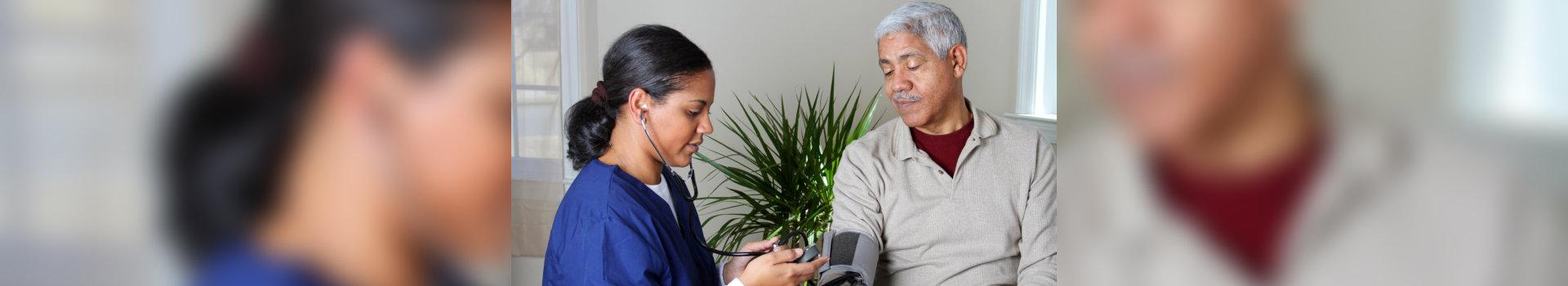 caregiver checking blood pressure of old man